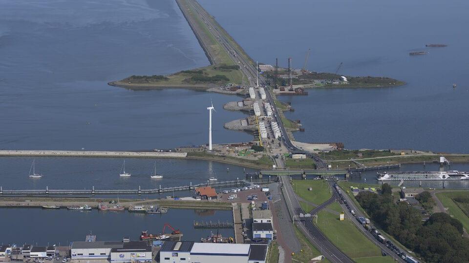 Van boven kijken we uit op de Afsluitdijk. We zien water, de weg en sluizen. Aan de zijkant zie je een windmolen.