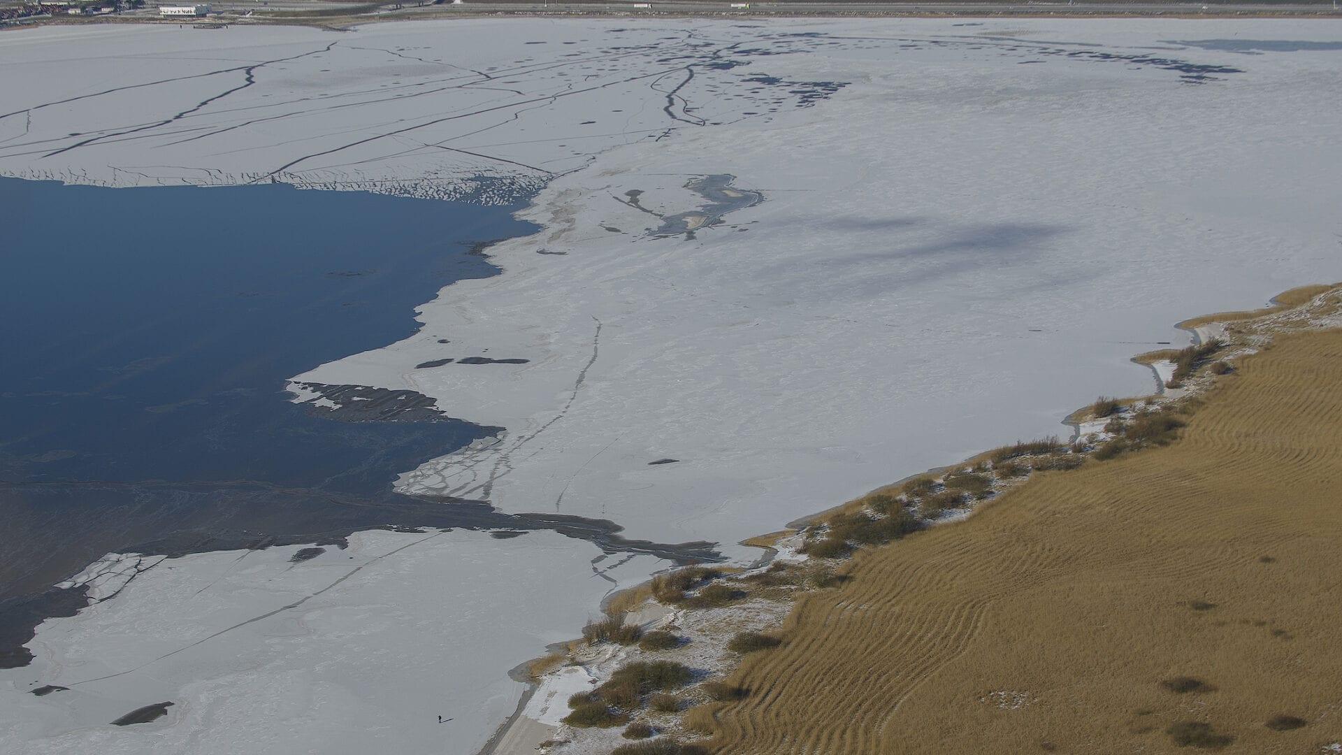 Luchtfoto Kornwerderzand. Het is winter en er ligt ijs op het IJsselmeer.
