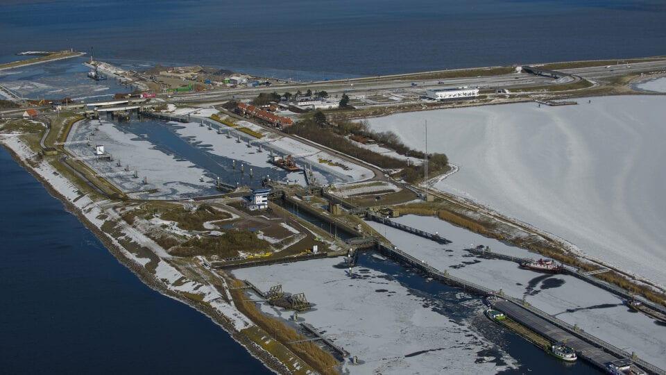 Luchtfoto van Kornwerderzand. Er ligt ijs bij de sluizen.