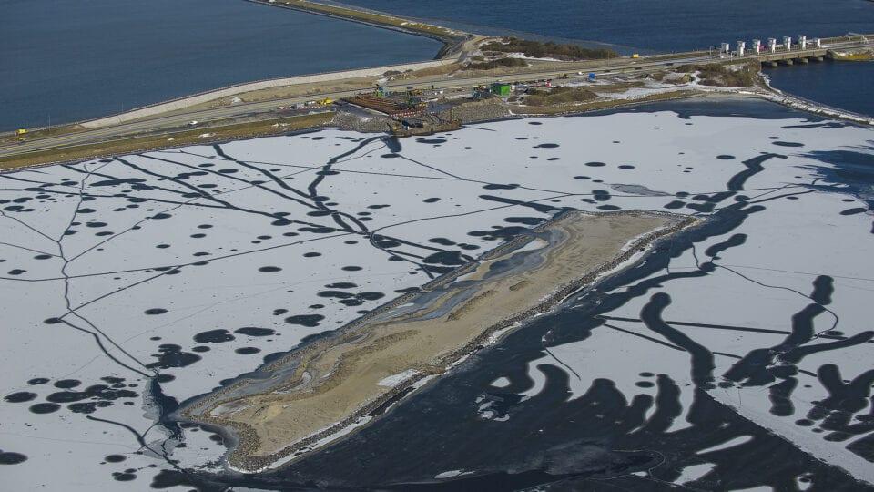 Luchtfoto van het werkeiland voor Windpark Fryslân bij Kornwerderzand. Het is winter.