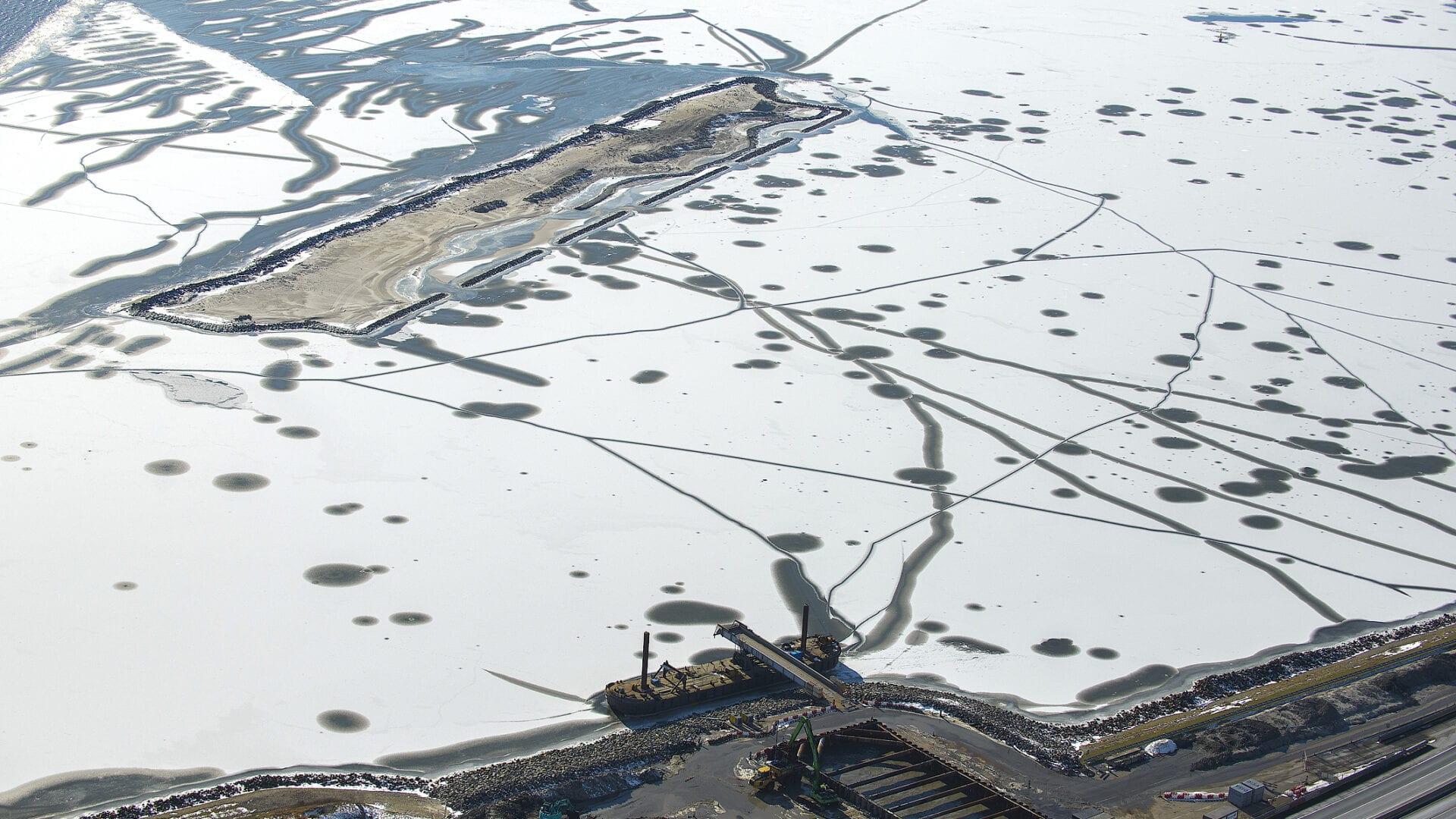 Het water naast de Afsluitdijk is voor een groot deel bevroren