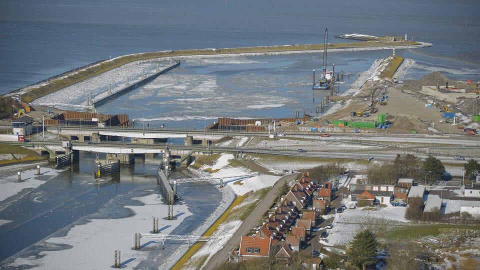 Luchtfoto van Kornwerderzand en de Afsluitdijk. Het is winter en we zien de sluizen.