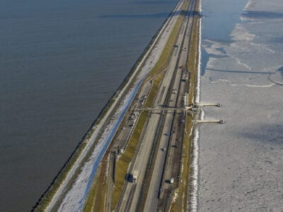 Luchtfoto van de Afsluitdijk in de winter. We kijken uit over het monument, de dijk en het water.