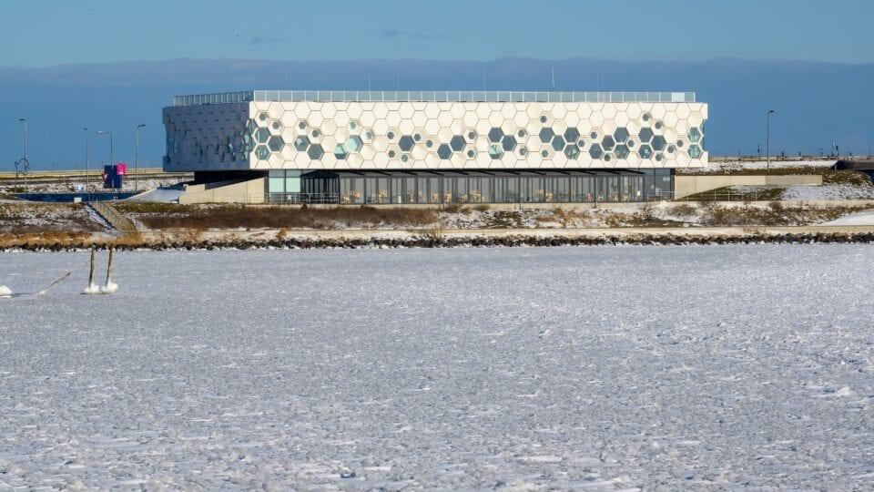 Luchtfoto van het Afsluitdijk Wadden Center. Het is winter en het centrum ligt achter het IJsselmeer.