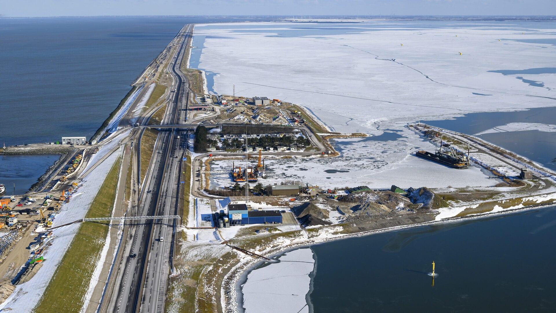 Een winterfoto uit de lucht van de Blue Energy Centrale. We zien de Afsluitdijk met water aan weerskanten.