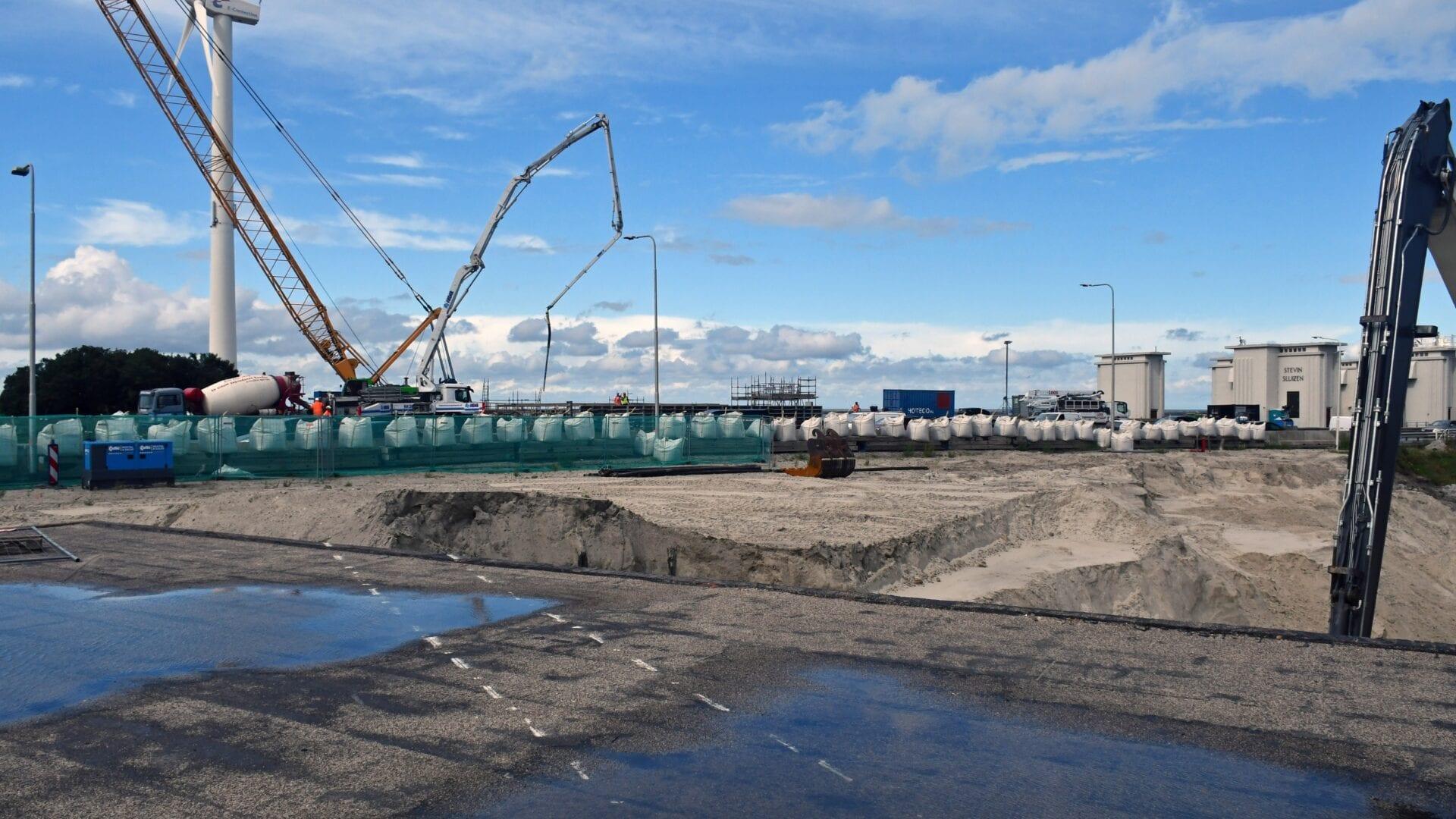 Op de foto zien we een werkterrein waar een deel van de Kazemat wordt weggehaald. We zien kranen en een plas water op de voorgrond.