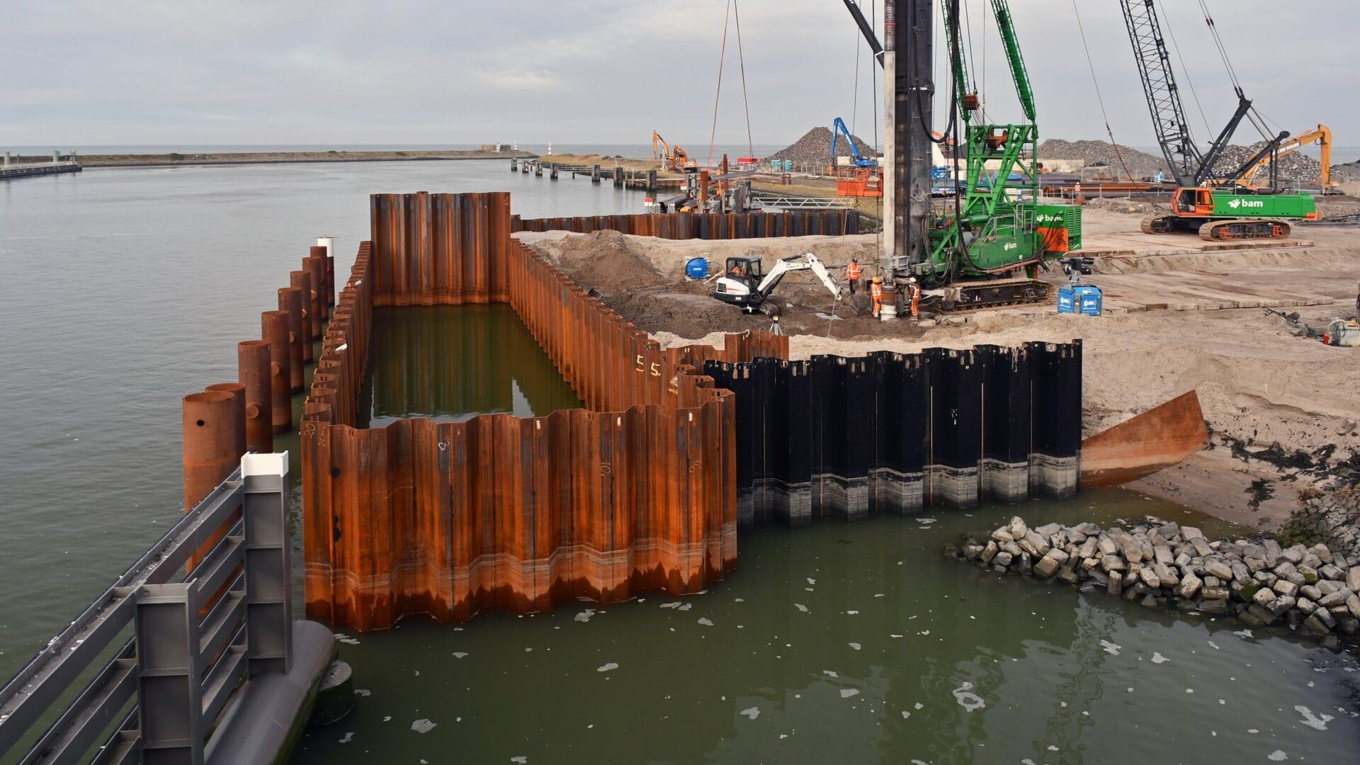 Op de foto zie je de BSFI-palen die in het water bij de keersluis van Kornwerderzand komen. De palen staan in een vierkant en vormen een gesloten ruimte in het water.