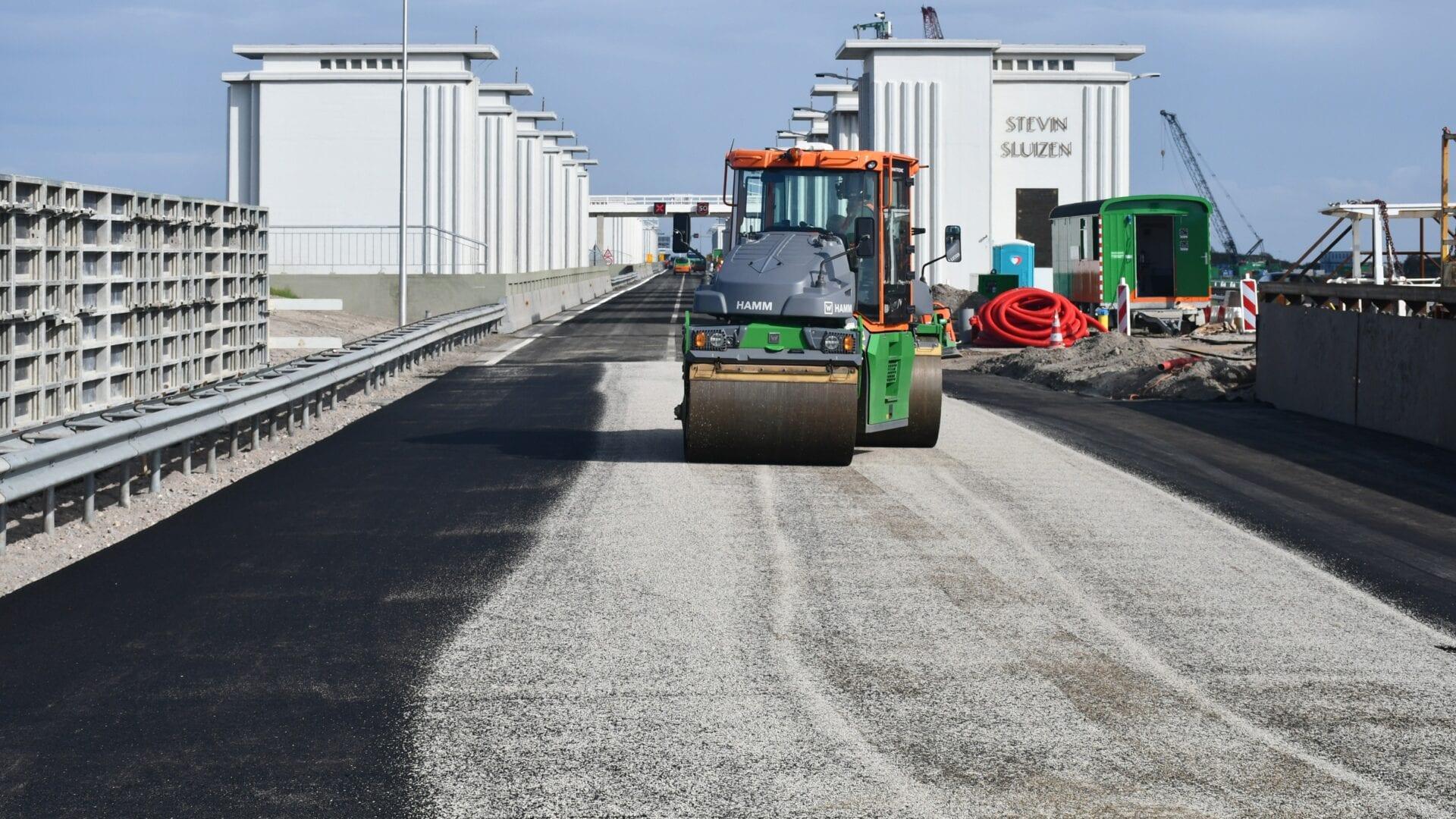 Op de foto zien we de weg van de Afsluitdijk. Op de weg zie je een asfaltwagen.