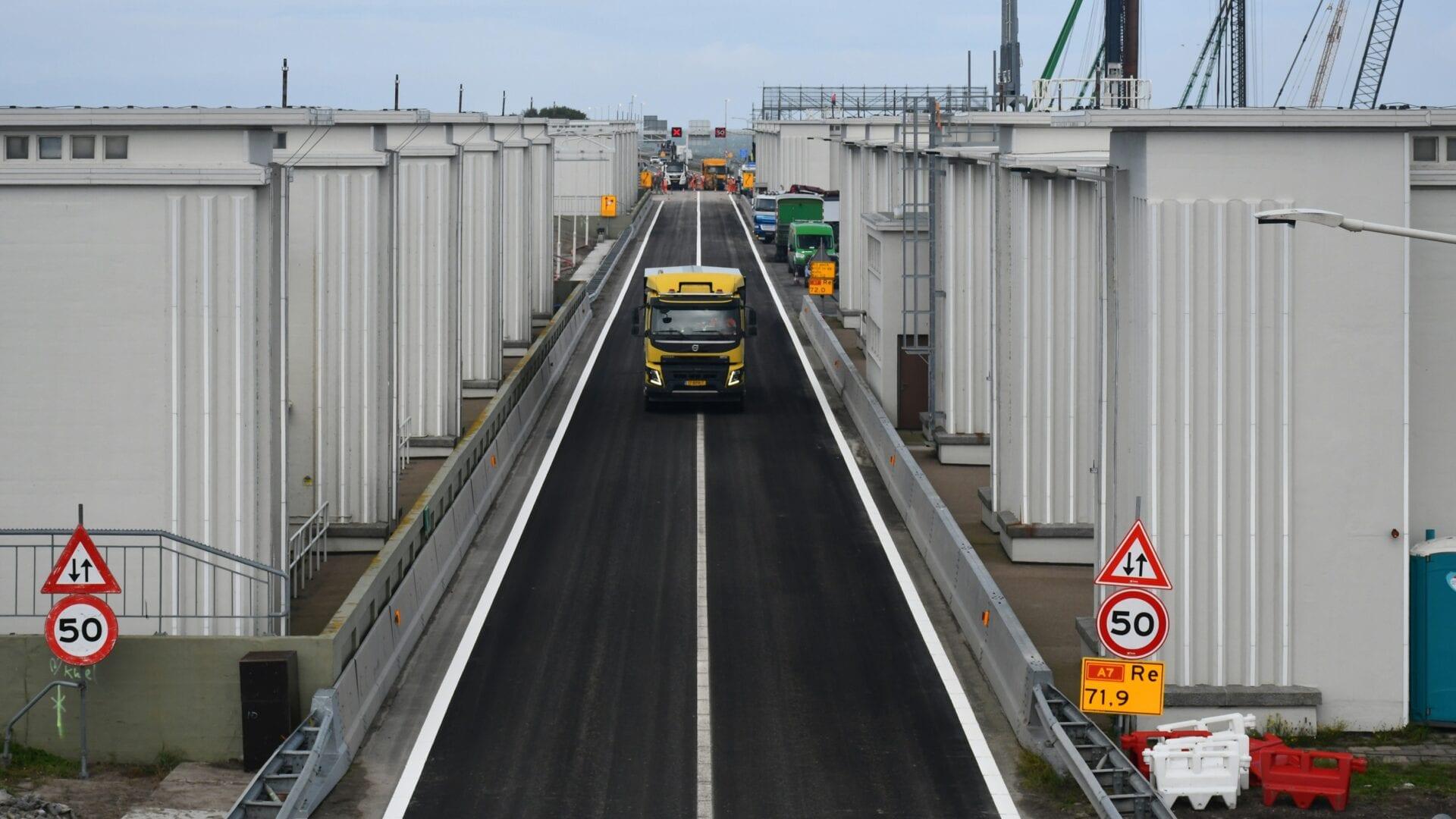 Op de foto zien we de weg van de Afsluitdijk. Op de weg zie je een vrachtwagen