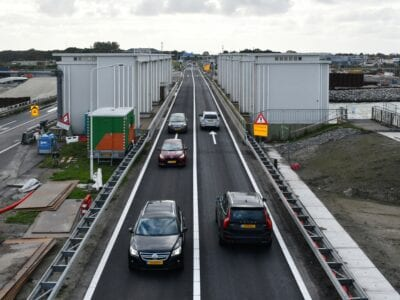 We zien de weg van de Afsluitdijk. Er rijden meerdere auto's overheen.