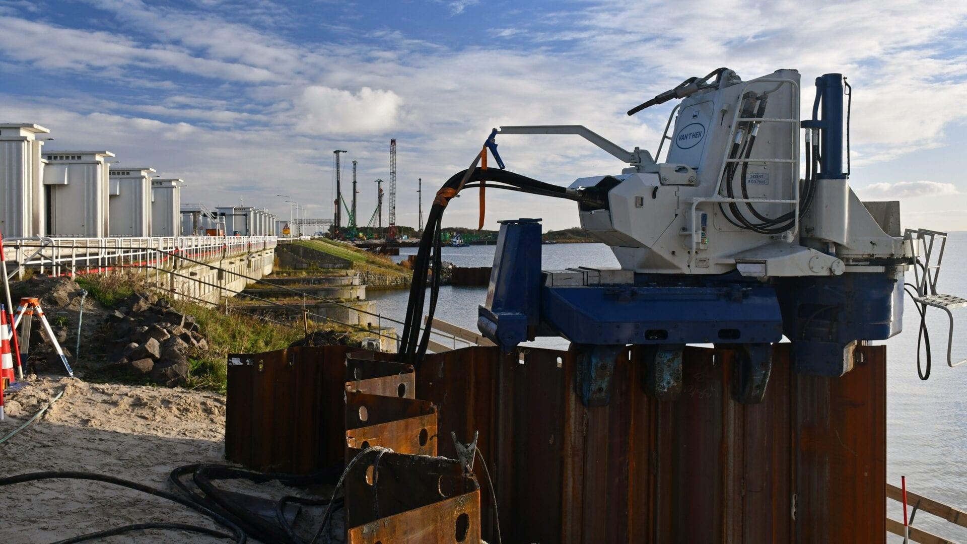 Op de foto zie een machine bezig met de damwanden. Dit zijn stalen constructies die op hun plek getild moeten worden.