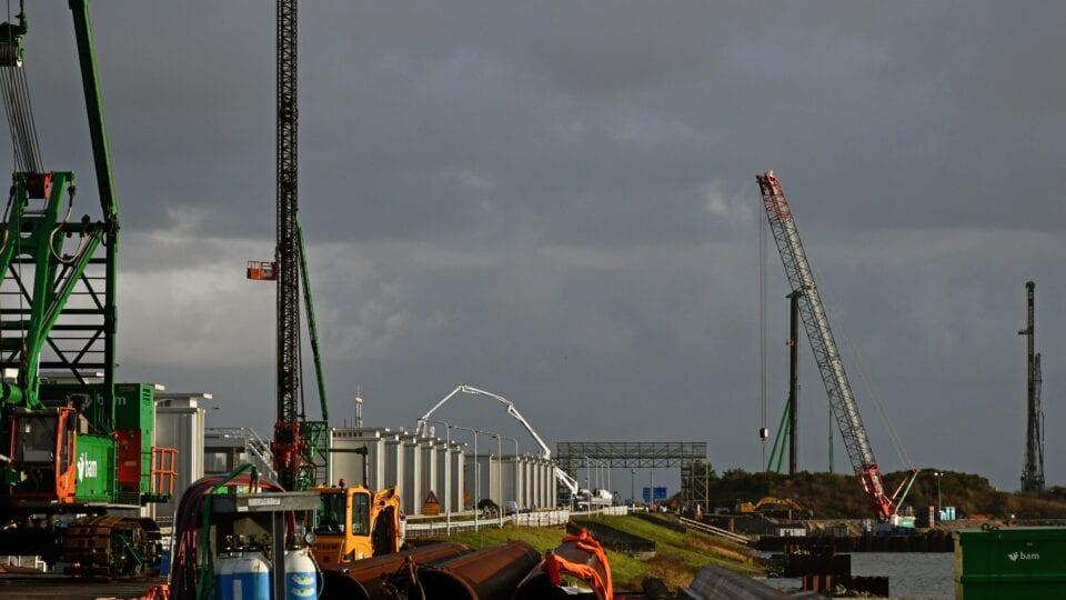 We kijken uit over de Afsluitdijk. Voor zien we kranen en machines, daar achter de witte gemaalgebouwen.