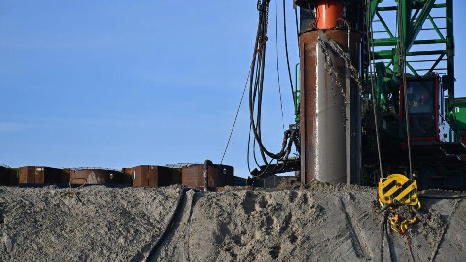 Eerste pompgemaal Den Oever; aan de IJsselmeerkant worden de stalen buispalen in de grond gebracht, deze vormen straks met de tussenliggende damwanden de bouwkuip, waar straks het instroomgedeelte van het gemaal wordt aangelegd.