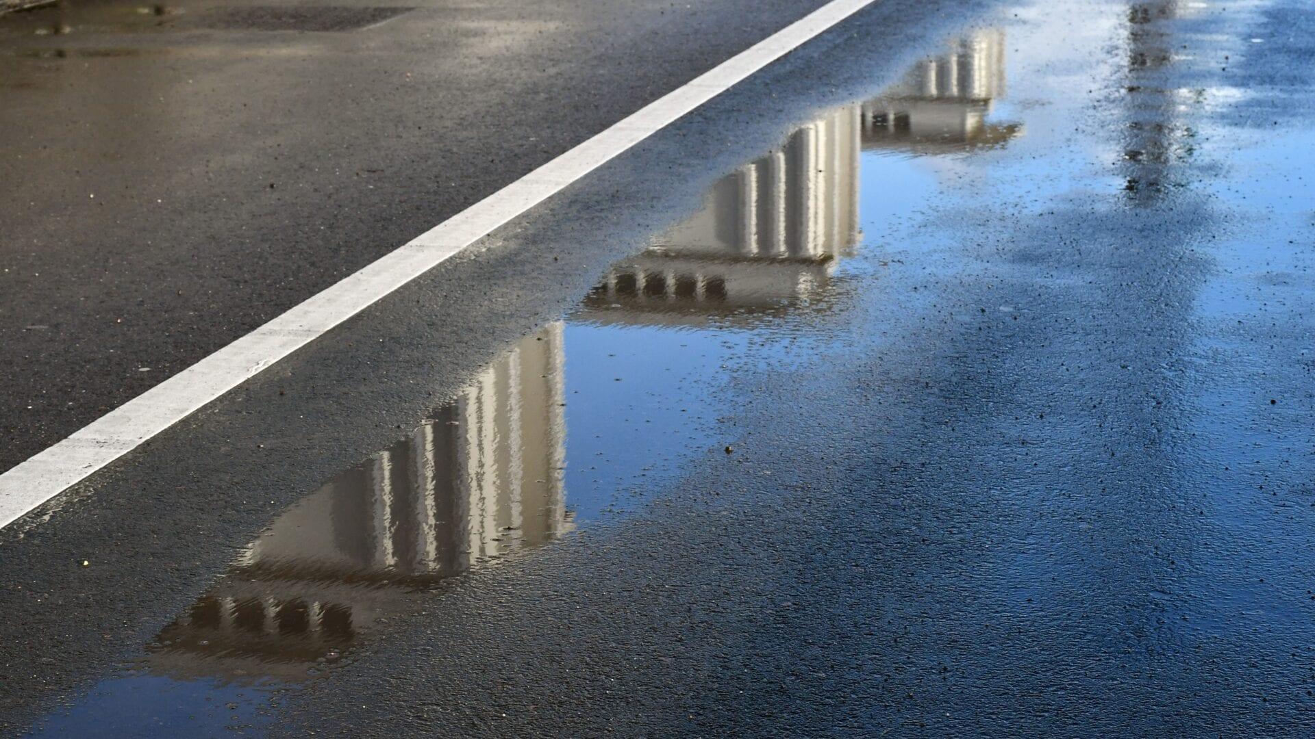 We zien de weg van de Afsluitdijk. Het is een close-up en er ligt water op de weg