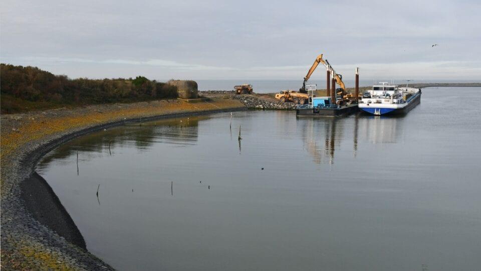 Op de afbeelding zie je een boot met een hijskraan bezig bij de coupure in de Afsluitdijk.