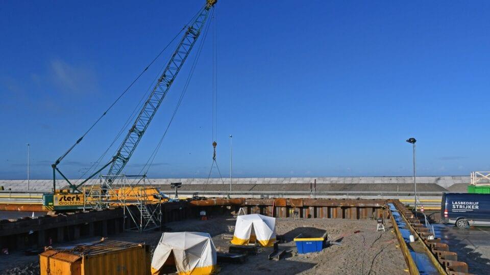 Coupure Vismigratie Rivier; voorbereidingen voor het ontgraven van de bouwkuip aan de kant van het IJsselmeer is gestart, het stempelraam wordt aangebracht met het benodigde laswerk dat onder de tentjes plaatsvindt.