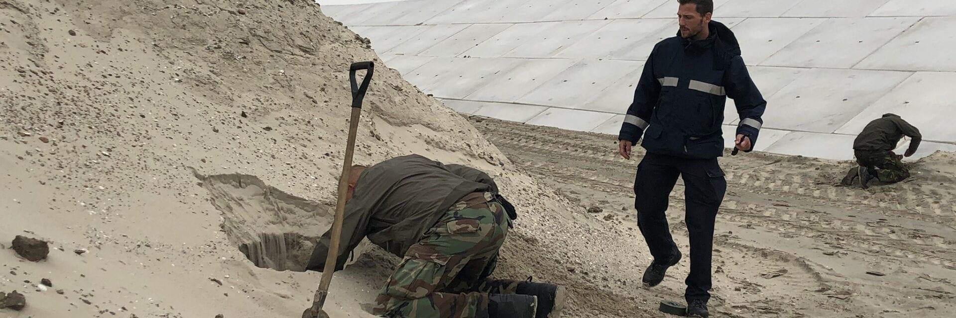 Op deze foto zie je een man op zijn knieën zitten in het zand van een soort duin, met een schep naast zich. En een andere man komt aanlopen. Je ziet stenen op de achtergrond.