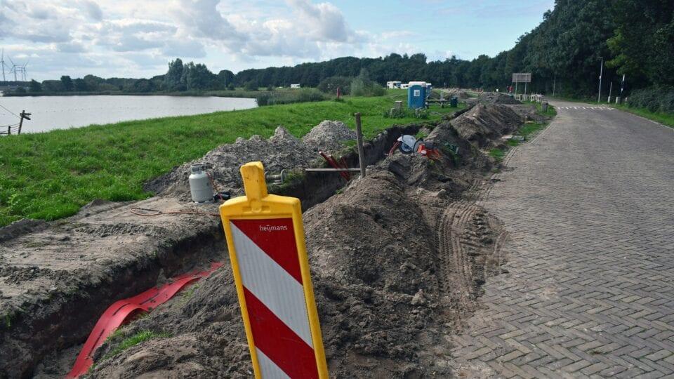 Op de foto zien we werkzaamheden aan de weg bij de Afsluitdijk. Vooraan staat een wit-rood gestreept verkeersbord.