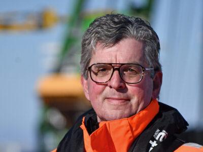 Op deze foto zie je Jan Wessels, de fotgraaf van De Afsluitdijk. Hij heeft een oranje jas aan, een camera om zijn net en een helm in de hand. Op de achtergrond zie je wazig een kraan
