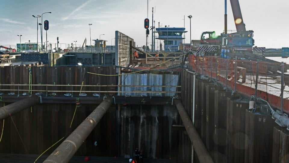 Keersluis Den Oever; terwijl de wapening voor de constructievloer onder in de bouwkuip wordt aangebracht, worden de stutten verwijderd. Na het aanstorten en uitharden van het beton zijn deze niet langer nodig.