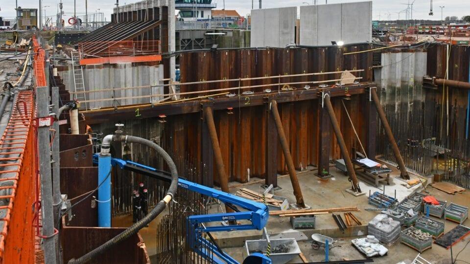 Keersluis Den Oever; aan de zijkanten van de bouwkuip voor de keersluis wordt bekisting aangebracht voor de keersluiswanden met behulp van kranen wordt het bekistingsmateriaal de bouwkuip in gehesen.