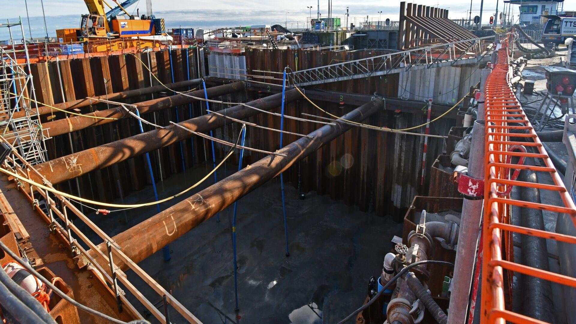 eersluis Den Oever; na de onderwaterbetonstort is de bouwkuip met gebruik van 16 bronnen leeggepompt. Ca. 5.000 m3 water (5 miljoen liter) is weggepompt en de vloer is schoongemaakt.