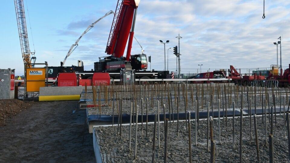 De betonnen prefab wandelementen van de technische ruimten met de uitstekende wapening liggen klaar om op hun plaats gehesen te worden.