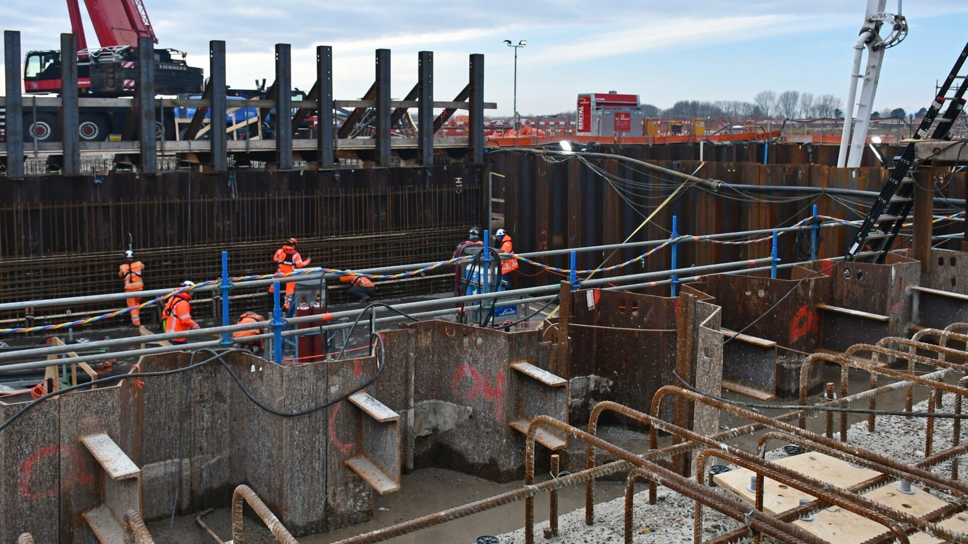Keersluis Den Oever; de stalen stutten waartegen de betonnen prefab wandelementen van de technische ruimten geplaatst worden. Op de voorgrond brengen de vlechters de wapening voor de nieuwe kademuur aan.