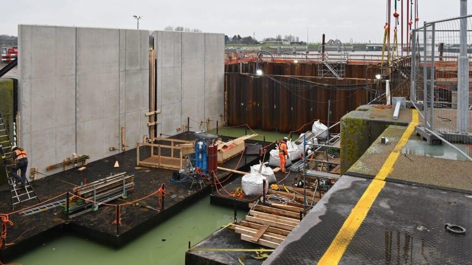 Keersluis Den Oever; de prefab betonnen wandelementen van de technische ruimten zijn op hun plaats gemonteerd, terwijl aan deze kant van de sluis de wapening van de kademuur wordt aangebracht.