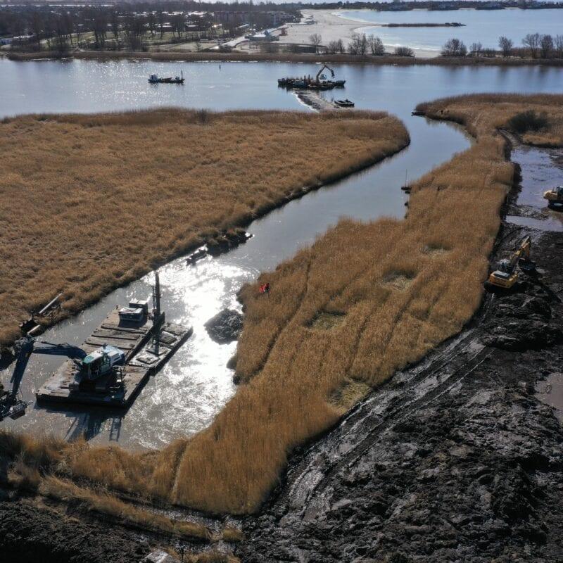 Op deze foto zie je vanaf boven water en land waar riet op staat dat eruit geschept wordt met kranen.