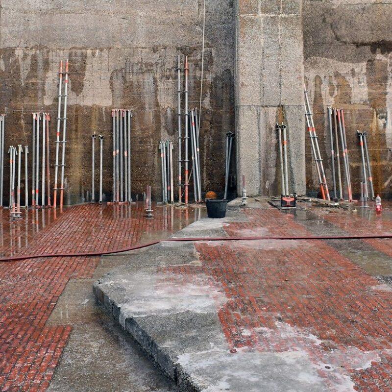 Op deze foto zie je de drooggepompte schutsluis van de Stevinsluis. Je ziet de muren en de vloer van rode gemetselde stenen.