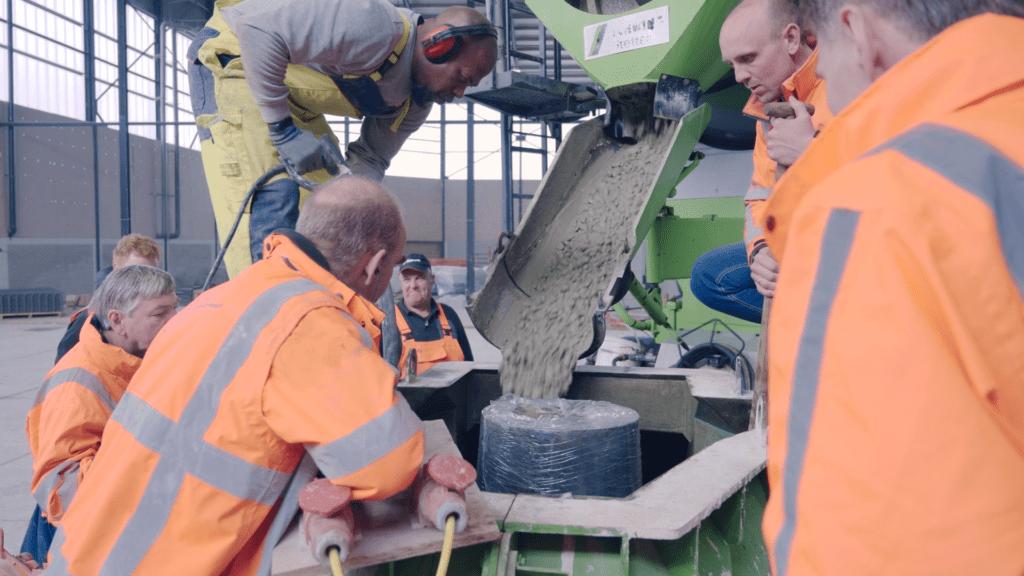 Op deze foto zie je een man staan achter een betonwagen waar beton uitstroomt.