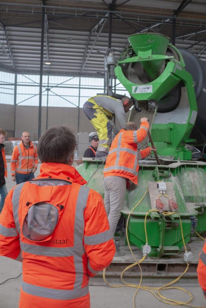 Op deze foto zie je meerdere mensen staan rondom een betonwagen. Een man schept beton in een kruiwagen.