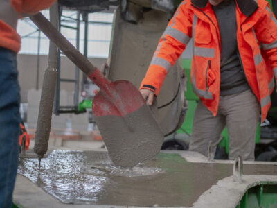 Op deze foto zie je twee mannen voor een betonwagen staan, een ervan schept met een schep beton in een kruiwagen.