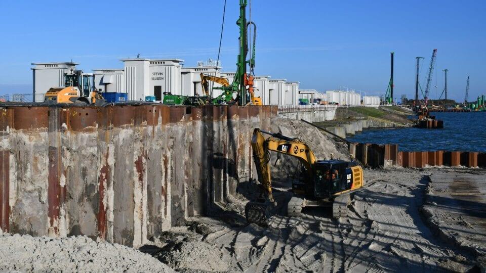 Eerste gemaal Den Oever; het zogenaamde compartimenteringsscherm (scheidingswand) tussen de bouwkuipen aan de kant van de Waddenzee en het IJsselmeer, bestaande uit buispalen en damwanden (combiwand) wordt gedeeltelijk ontgraven. In de verte de werkzaamheden aan het tweede gemaal.