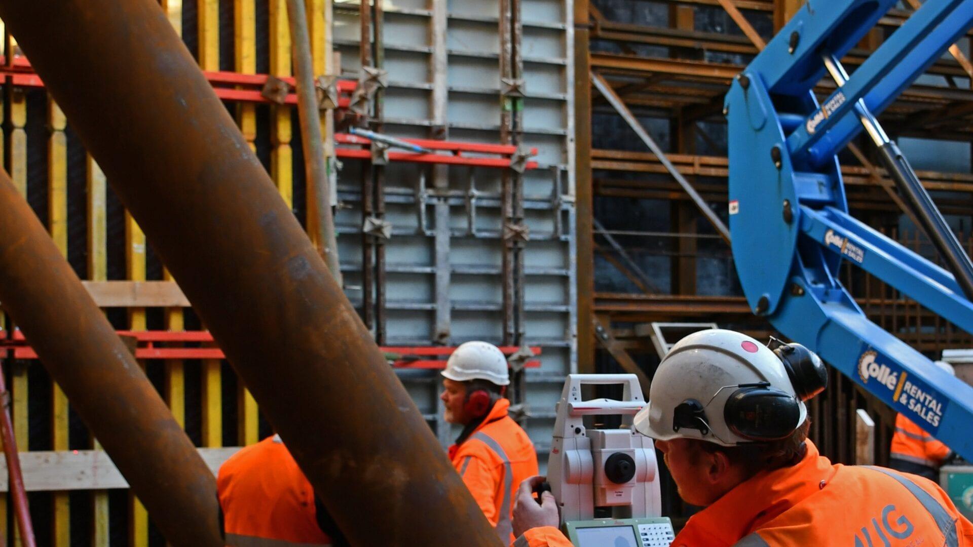 Keersluis Den Oever; aan de zijkanten van de bouwkuip voor de keersluis wordt bekisting aangebracht voor de keersluiswanden met behulp van kranen wordt het bekistingsmateriaal de bouwkuip ingehesen