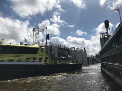 Op deze zie je een boot van rijkswaterstaat door de geopende sluisdeuren van de Stevinsluizen varen.