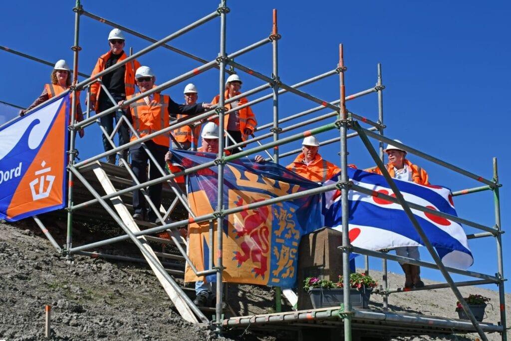 Op deze foto zie je een delegatie van gedeputeerden en RWS collega's bij de nieuwe onthulling van de gerestaureerde grenspaal Ze staan op een stelling en je ziet vlaggen van Friesland en Noord-Holland.