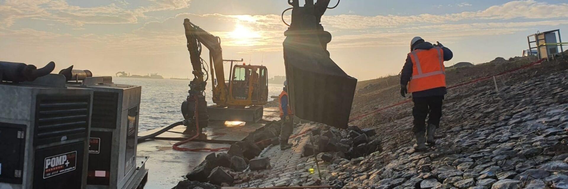 Op deze foto zie je de dijk aan IJsselmeerzijde waaraan gewerkt wordt. Je ziet een shovel, dijkbekleding en een man aan het werk.