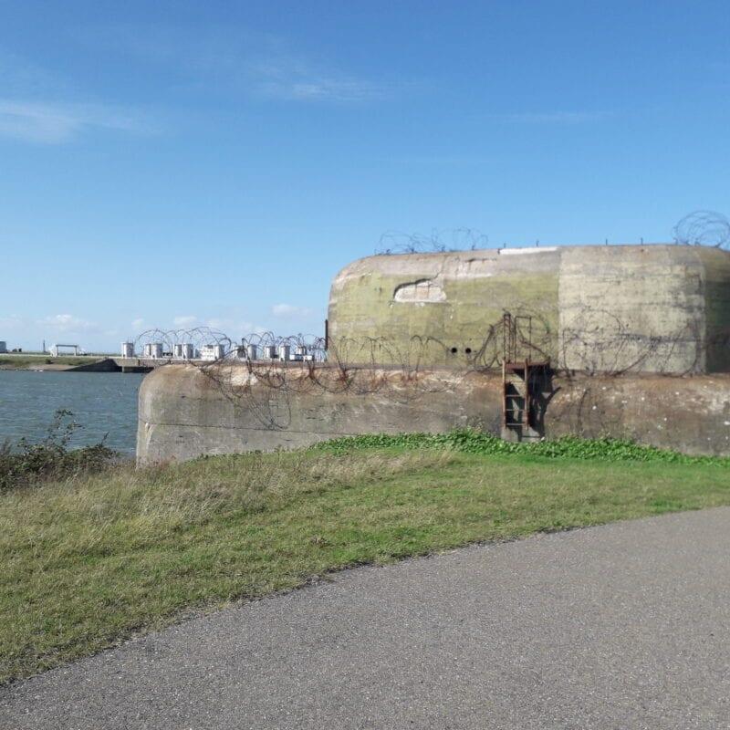 Op de foto zien we de Kazemat bij Kornwerderzand. Hij staat voor het water en de Afsluitdijk.