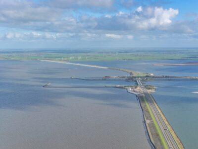 Luchtfoto van de Afsluitdijk met uitzicht over weg en water