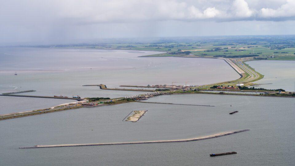 Uitzicht op de Afsluitdijk met rechts Kornwerderzand en voorin de landtong voor de Vismigratierivier.