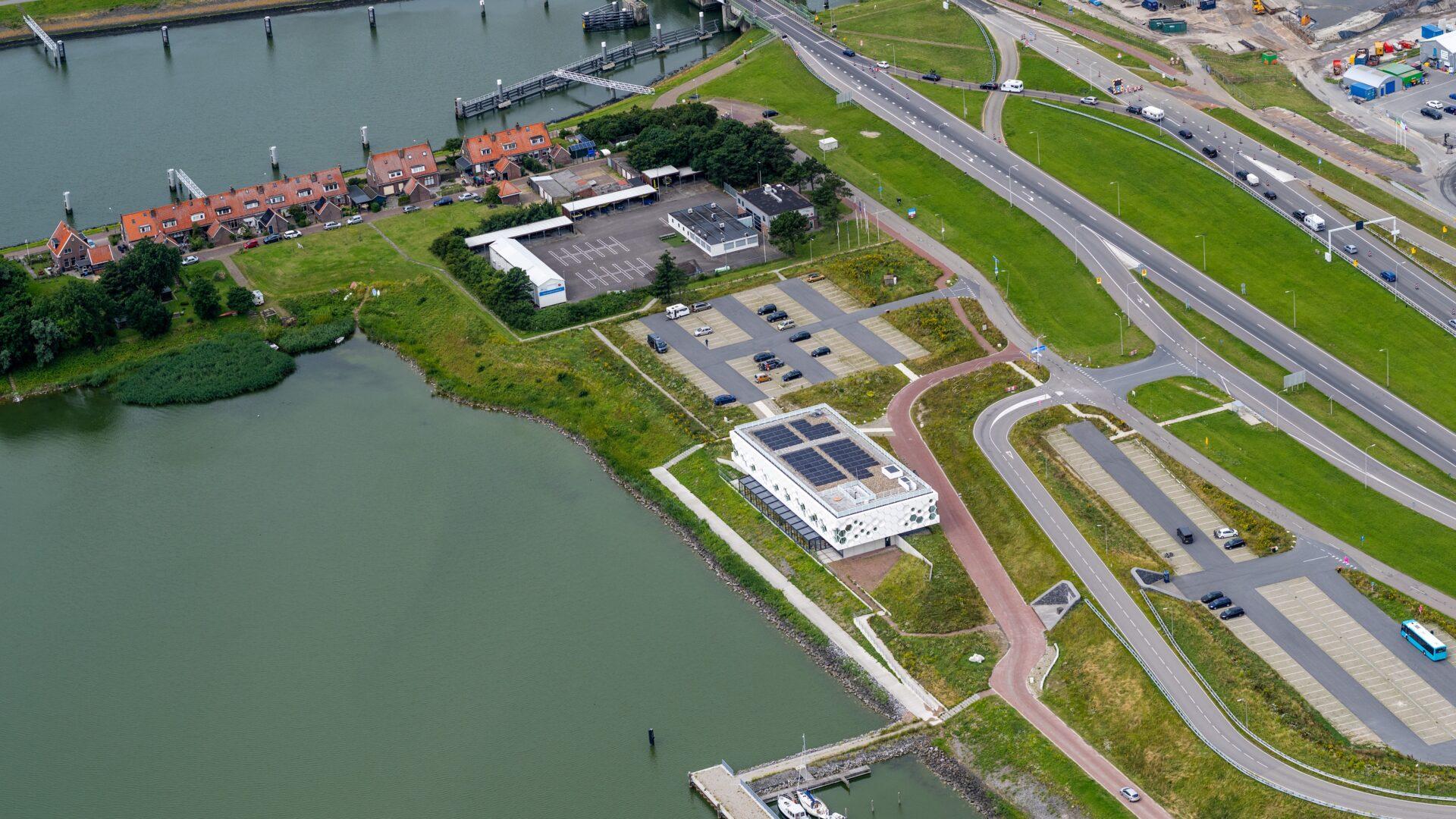 Van boven zien we het Afsluitdijk Wadden Center en een deel van de oranje huizen bij Kornwerderzand