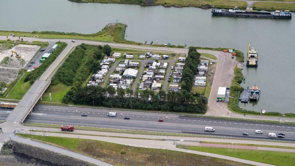 De camping op de Afsluitdijk. Diverse witte gebouwen naast het water.