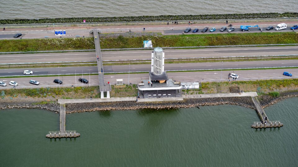 We zien een stukje Afsluitdijk bij het Monument. De witte toren staan in het midden van de foto.