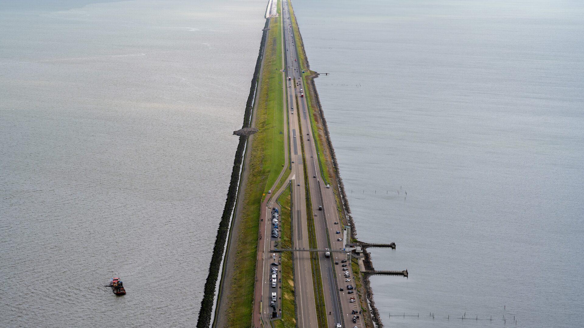Uitzicht van boven op de Afsluitdijk. We zien een lange strook weg.