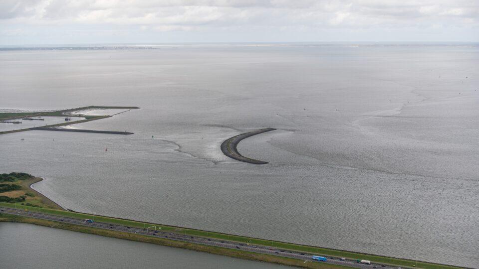 We zien een stukje weg van de Afsluitdijk. Bovenin zie je een ronde landtong in het water van de Waddenzee.