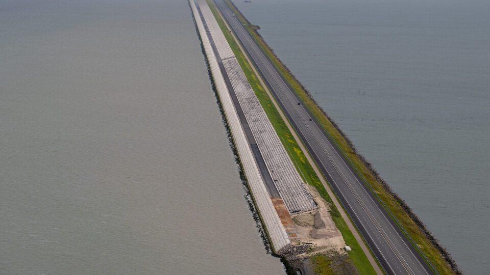 Van boven kijken we op de Afsluitdijk. Aan de waddenzeekant zie je de nieuwe bekleding