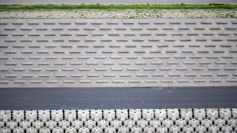 Van boven kijken we over de nieuwe weg van de Afsluitdijk. Je hebt uitzicht over nieuwe bekleding